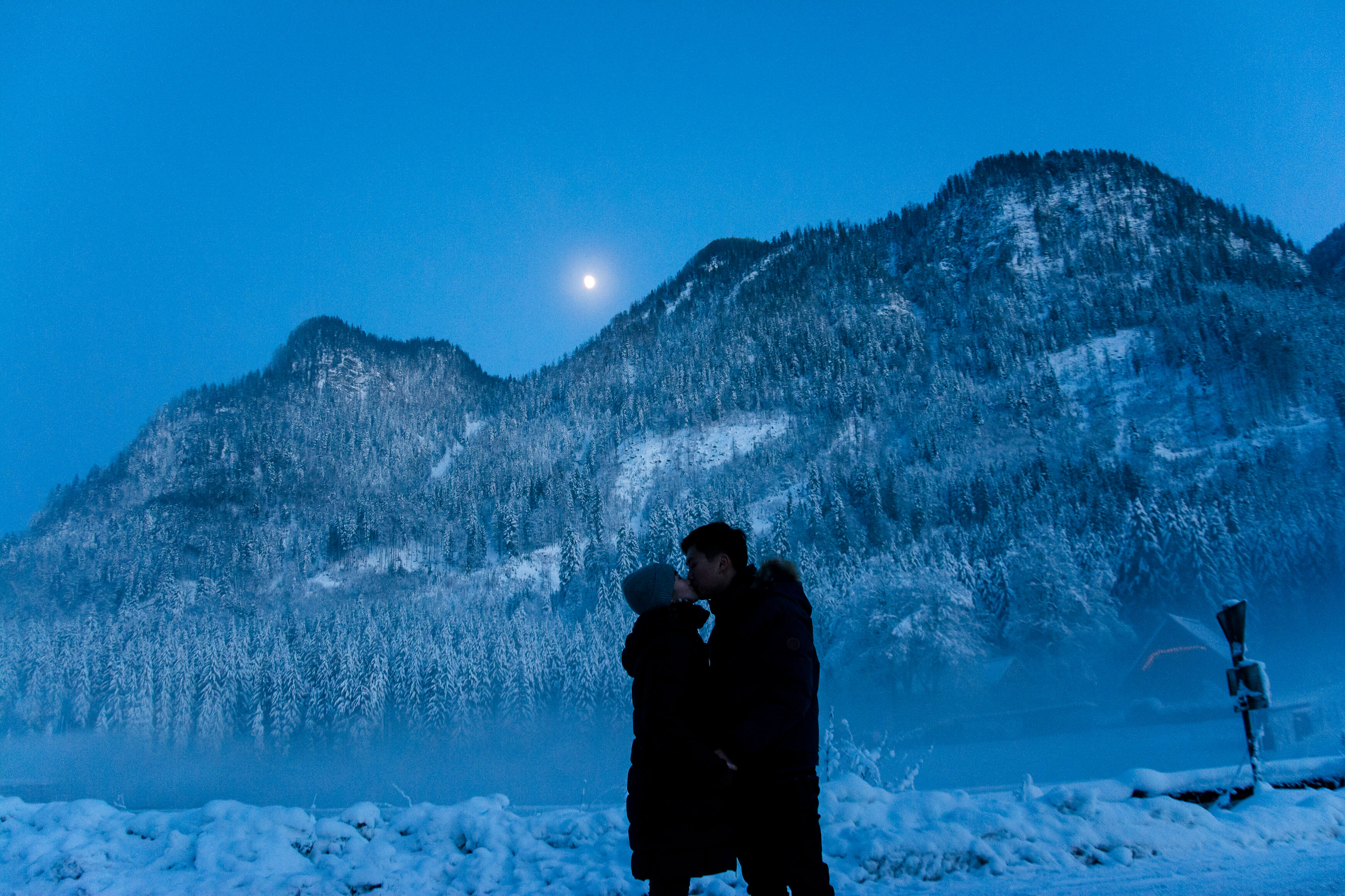 Wonderful engagement pictures in the snow and the moon in the background